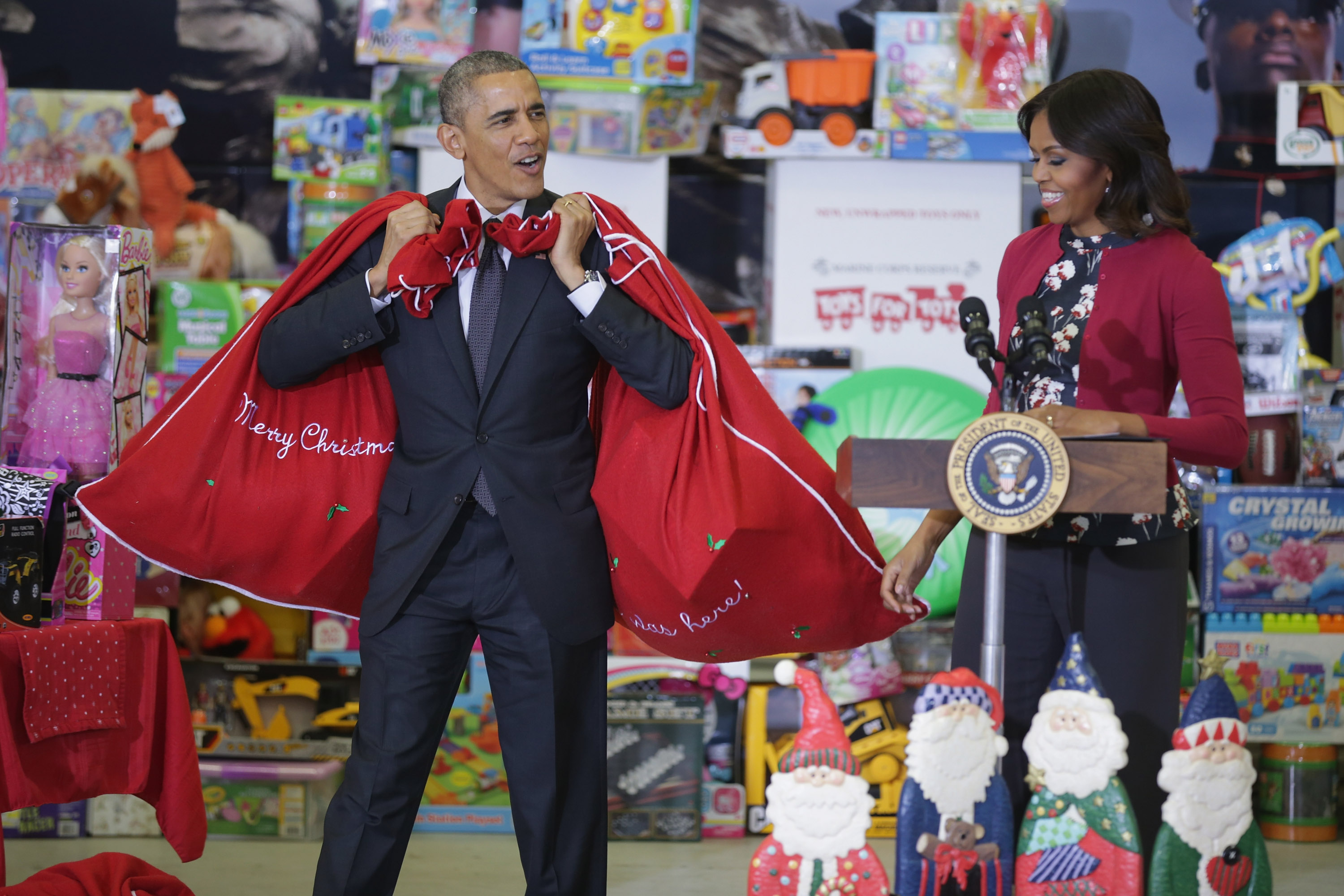WASHINGTON, DC - DECEMBER 10: U.S. President Barack Obama (L) and first lady Michelle Obama deliver toys and gifts donated by Executive Office of the President staff to the Marine Corps Reserve Toys for Tots Program at Joint Base Anacostia-Bolling on December 10, 2014 in Washington, DC. For 67 years the Toys for Tots program has worked with local communities to collect and distribute toys and gifts for less fortunate children throughout the United States. (Photo by Chip Somodevilla/Getty Images)