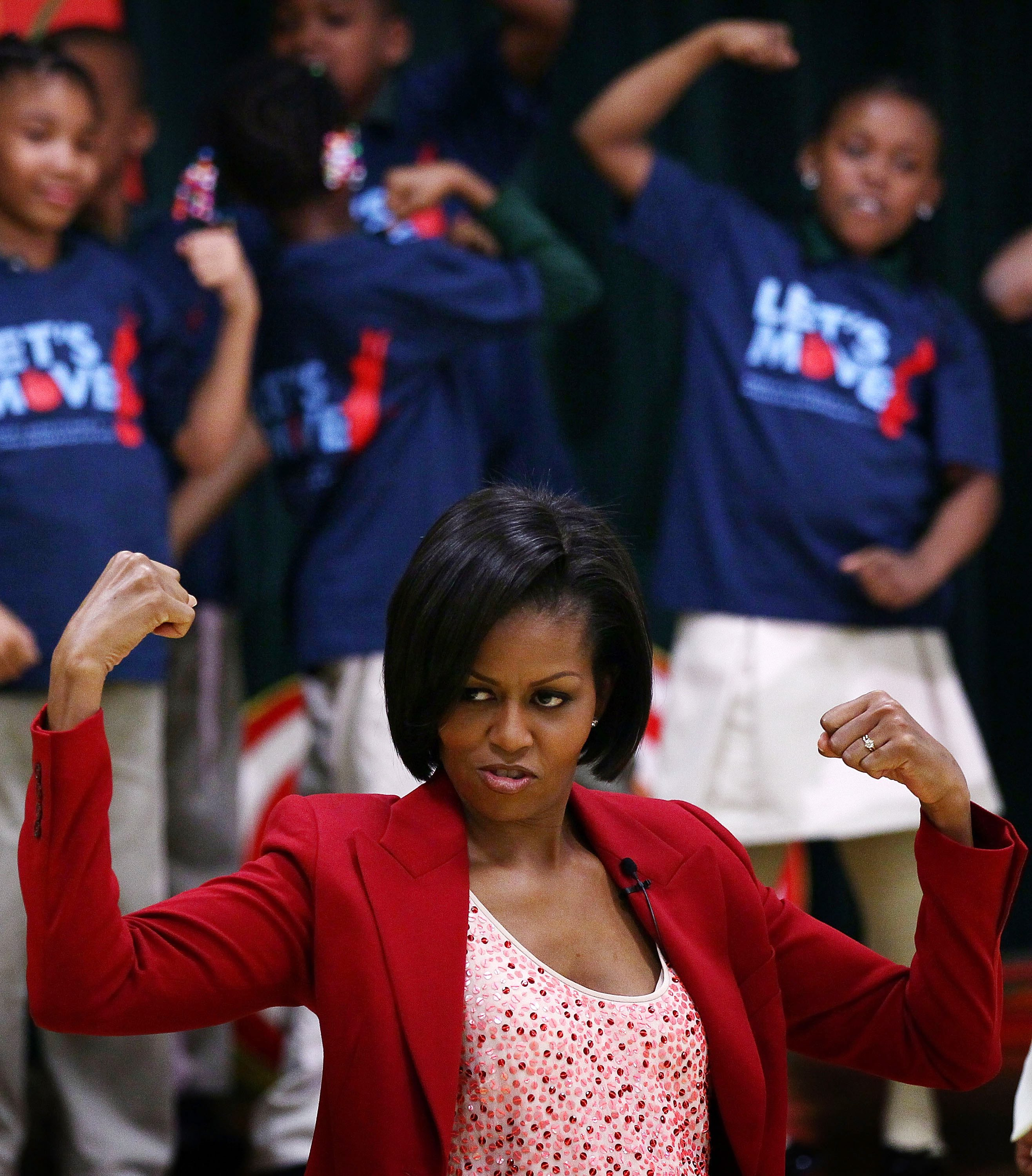 "WASHINGTON - APRIL 21: U.S. first lady Michelle Obama flexes her muscles as she exercises with schoolchildren at the River Terrace School April 21, 2010 in Washington, DC. Mrs. Obama visited the school to highlight physical activity as a critical element of the ""Let's Move!"" initiative with several Olympians and Paralympians, including 2010 Olympians Shani Davis and Hannah Kearney and 2010 Paralympians Alana Nichols and Heath Calhoun. (Photo by Win McNamee/Getty Images)"