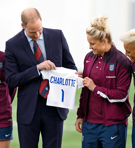 BURTON-UPON-TRENT, UNITED KINGDOM - MAY 20: (EMBARGOED FOR PUBLICATION IN UK NEWSPAPERS UNTIL 48 HOURS AFTER CREATE DATE AND TIME) Prince William, Duke of Cambridge receives an England football shirt for daughter Princess Charlotte of Cambridge from Captain Steph Houghton as he meets the England Women's Football Team at St George's Park on May 20, 2015 in Burton-upon-Trent, England. (Photo by Max Mumby/Indigo/Getty Images)