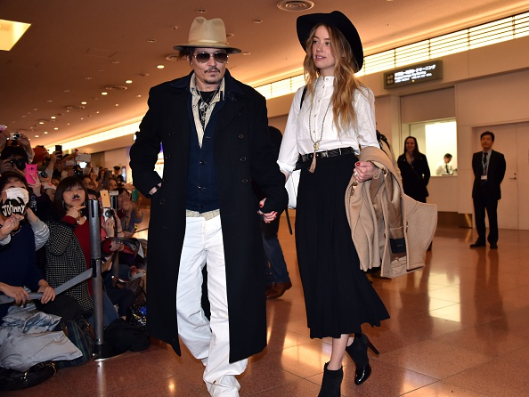 """US actor Johnny Depp (L), accompanied by his fiancee US actress and model Amber Heard (R), arrive at Tokyo International Airport on January 26, 2015 for the Japan premiere of his latest movie """"Mortdecai"""".  The action comedy movie will be screened in Japan from February 6.  AFP PHOTO        (Photo credit should read YOSHIKAZU TSUNO/AFP/Getty Images)"""