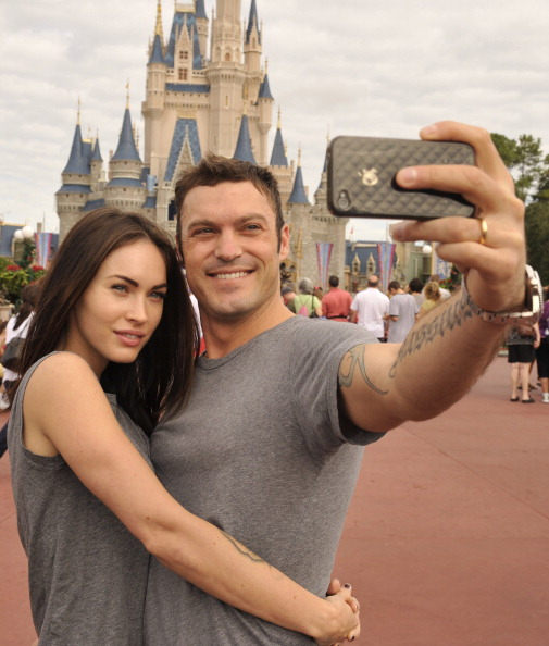 """LAKE BUENA VISTA, FL - NOVEMBER 26:  In this handout photo provided by Disney, actor Brian Austin Green (right) and his wife, actress/model Megan Fox (left), take a souvenir photo in the Magic Kingdom November 26, 2010 in Lake Buena Vista, Florida.  Green (""""Beverly Hills, 90210"""", """"Desperate Housewives"""") and Fox (""""Transformers,"""" """"Transformers: Revenge of the Fallen"""") were married in June 2010 in Hawaii.  (Photo by Gene Duncan/Disney via Getty Images)"""