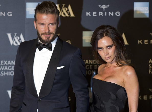 Former England footballer David Beckham (L) and his wife fashion designer Victoria Beckham pose for pictures as they arrive on the red carpet for the 'Alexander McQueen: Savage Beauty Gala' at the Victorian & Albert Museum in London on March 12, 2015. AFP PHOTO / JUSTIN TALLIS        (Photo credit should read JUSTIN TALLIS/AFP/Getty Images)