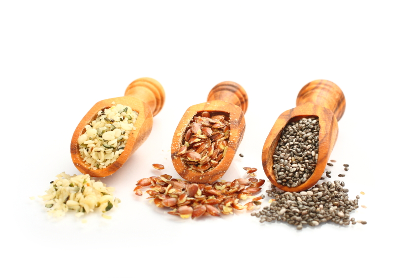 Superfoods in wooden scoops, one of the superfoods (seeds of chia, hemp and flax)