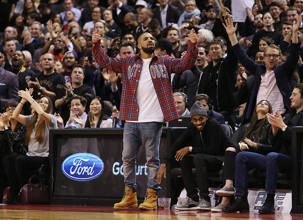 TORONTO, ON - NOVEMBER 25: Singer Drake celebrates a Raptors score on 'Drake Night' during an NBA game between the Cleveland Cavaliers and the Toronto Raptors at the Air Canada Centre on November 25, 2015 in Toronto, Ontario, Canada. NOTE TO USER: User expressly acknowledges and agrees that, by downloading and or using this photograph, User is consenting to the terms and conditions of the Getty Images License Agreement. (Photo by Vaughn Ridley/Getty Images)