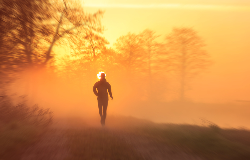 Sports concept: runner on a gravel road during a foggy, spring sunrise in the countryside.