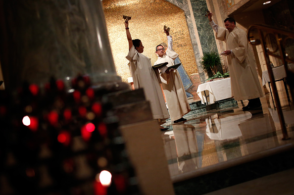 WASHINGTON, DC - MARCH 24: Altar servers ring bells during the start of the Mass of the Lord's Supper on Holy Thursday at the Cathedral of St. Matthew the Apostle March 24, 2016 in Washington, DC. During the mass, Cardinal Donald Wuerl, archbishop of Washington, washed the feet of 12 people, as Christ is said to have washed the feet of the apostles at the Last Supper. (Photo by Win McNamee/Getty Images)