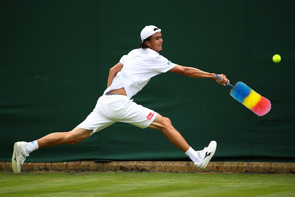LONDON, ENGLAND - JUNE 28: Taro Daniel of Japan stretches to play a backhand during the Men's Singles first round match against Juan Monaco of Argentina on day two of the Wimbledon Lawn Tennis Championships at the All England Lawn Tennis and Croquet Club on June 28, 2016 in London, England. (Photo by Clive Brunskill/Getty Images)