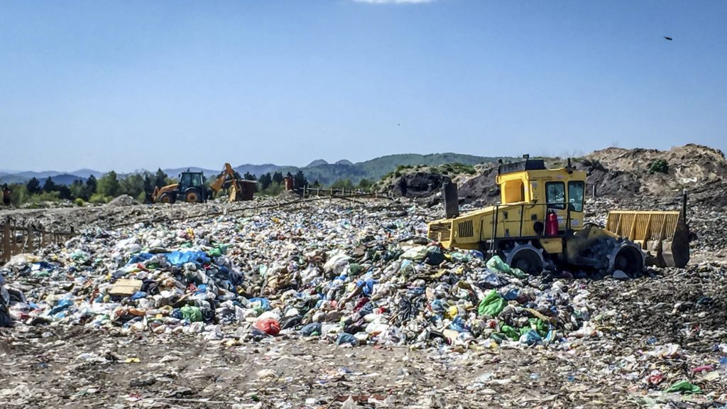Caterpillar compactor working in a landfill.