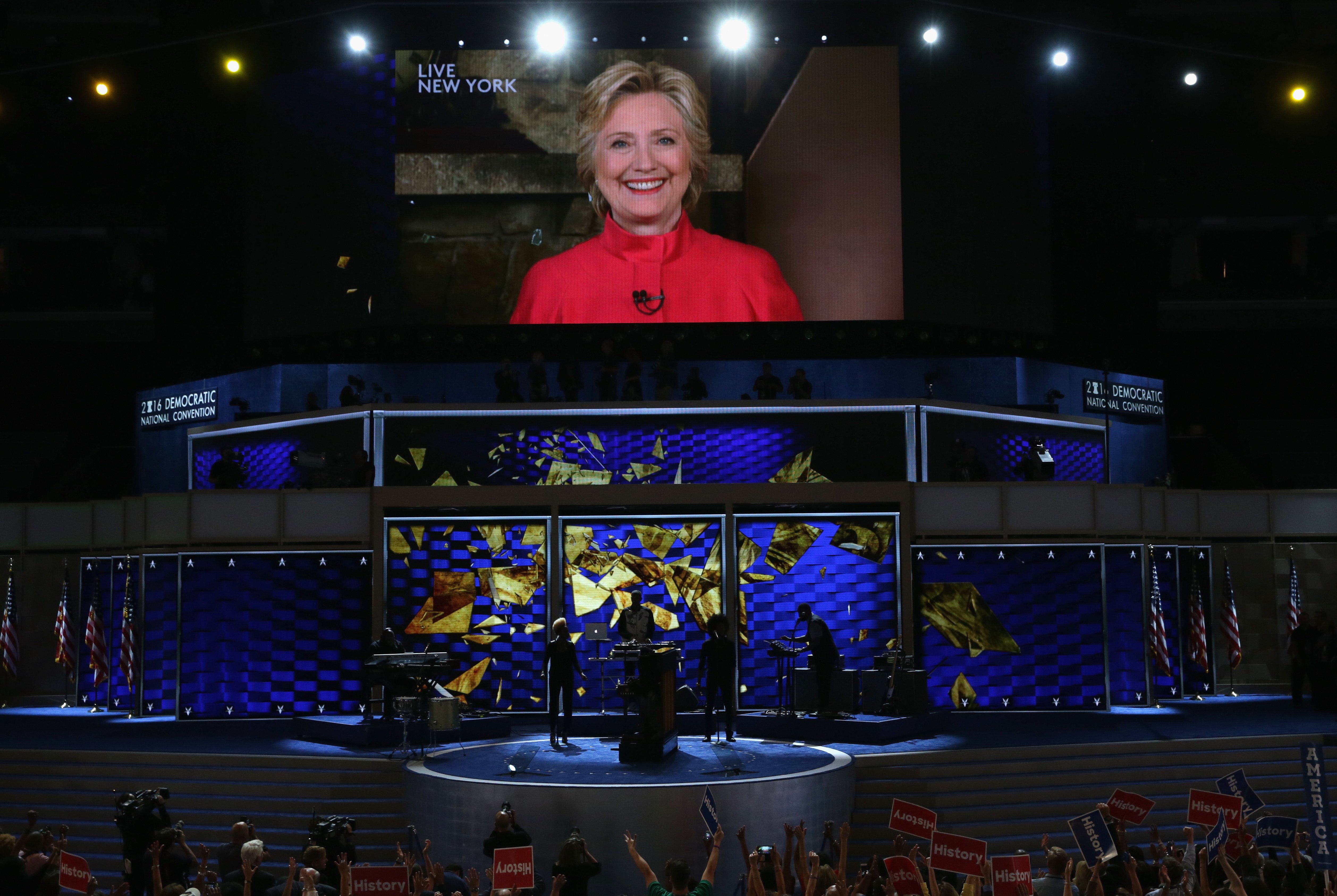 PHILADELPHIA, PA - JULY 26: Delegates cheer as a screen displays Democratic presidential candidate Hillary Clinton delivering remarks to the crowd during the evening session on the second day of the Democratic National Convention at the Wells Fargo Center, July 26, 2016 in Philadelphia, Pennsylvania. Democratic presidential candidate Hillary Clinton received the number of votes needed to secure the party's nomination. An estimated 50,000 people are expected in Philadelphia, including hundreds of protesters and members of the media. The four-day Democratic National Convention kicked off July 25. (Photo by Alex Wong/Getty Images)