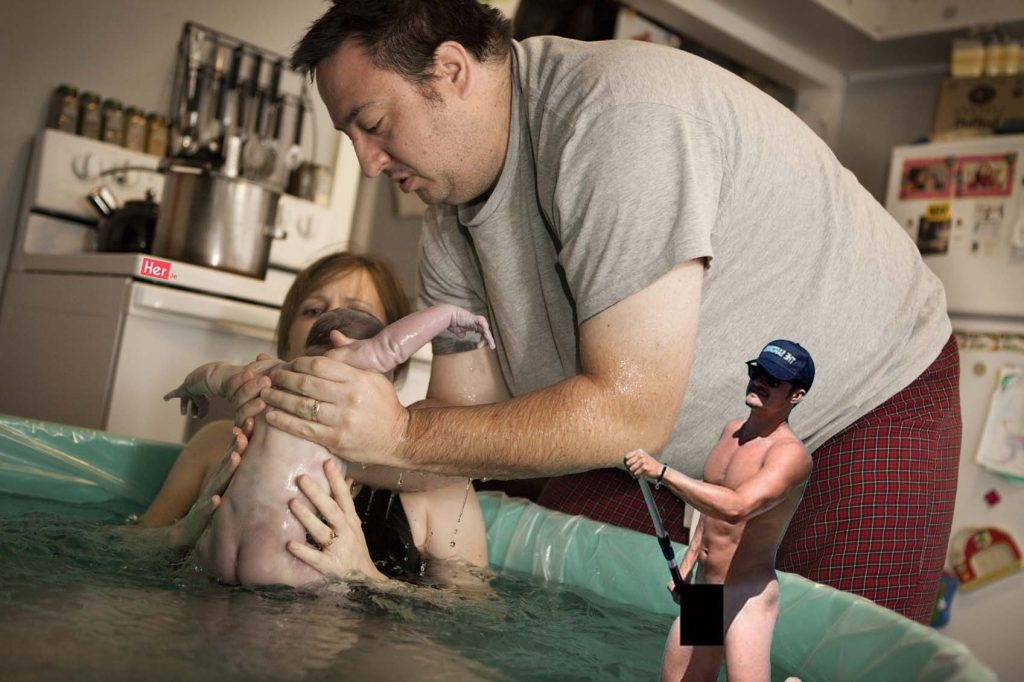 Color photo of a father taking his newborn baby son from the water of a birthing tub immediately after he was born in a water birth at home.