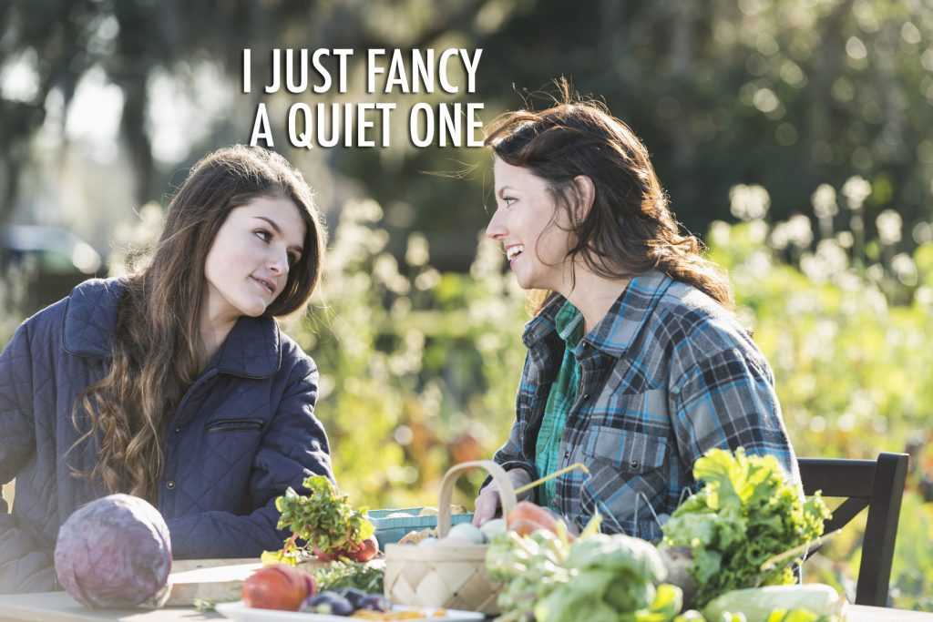 Mother and daughter sitting at a table outdoors on an organic farm, conversing on a bright, sunny day. On the table is fresh produce, including purple cabbage, radishes, leafy green vegetables, and a basket of eggs.