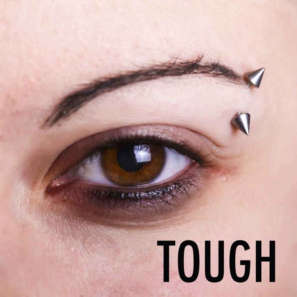 Brown female eye with an eyebrow piercing