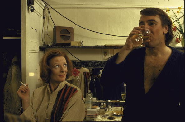 Actress Maggie Smith smoking a cigarette in her dressing room with her husband actor Robert Stephens as he enjoys a glass of wine during a break from the play Beaux' Stratagem at the Old Vic Theatre. (Photo by John Olson/The LIFE Picture Collection/Getty Images)
