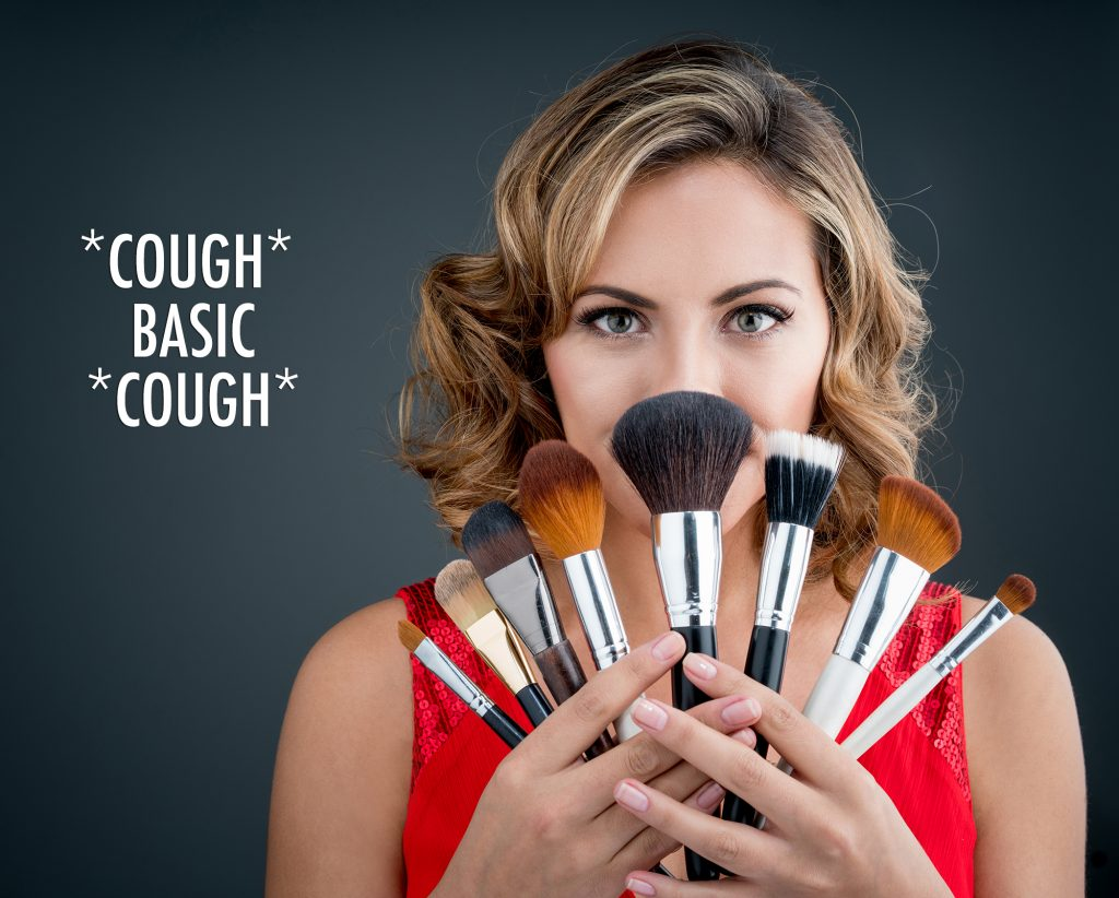 Excited woman holding makeup brushes and covering her face - beauty concepts