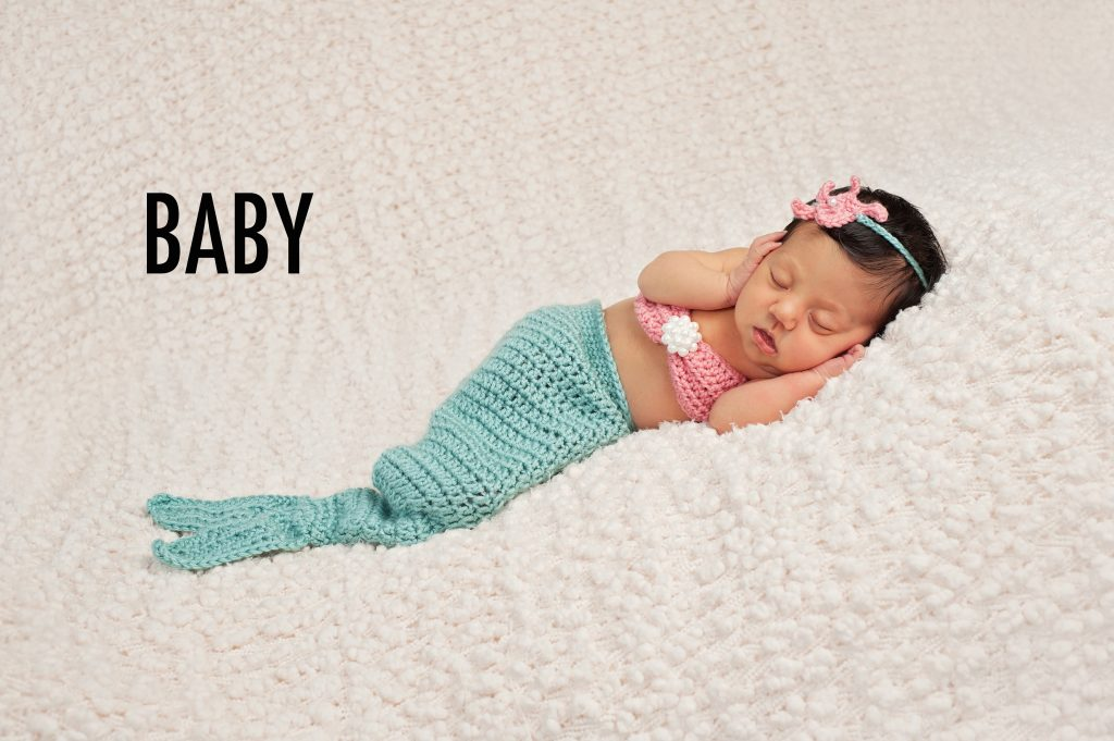 Newborn baby girl wearing a crocheted teal and coral colored mermaid costume. She is sleeping on a cream colored bouncle textured blanket.