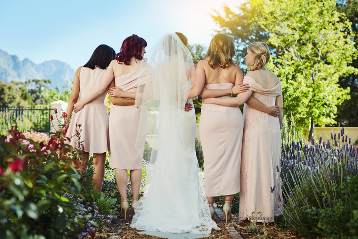 Rearview shot of a young bride and her bride's maids standing together outside during the day