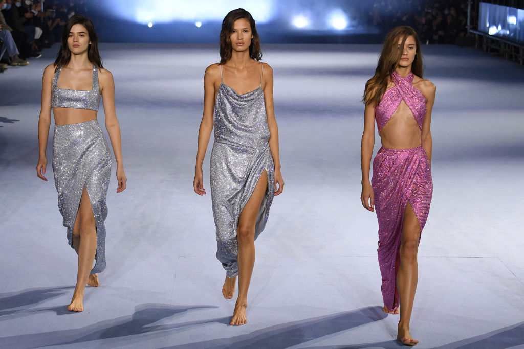 Three barefoot models wearing sequins on the runway